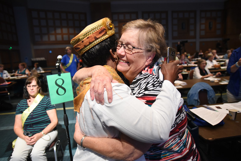Tenth Triennial Convention | Ruthie Dell Fairchild, Rockford, Ill. embraces Mary Jo Mettler after her update about solar panels for Phebe Hospital, Liberia.