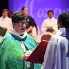 Tenth Triennial Gathering | Bishop Eaton proclaims the Gospel, John 4:5-26, as Valora Starr, holds the St. John's Gospel book in opening worship.