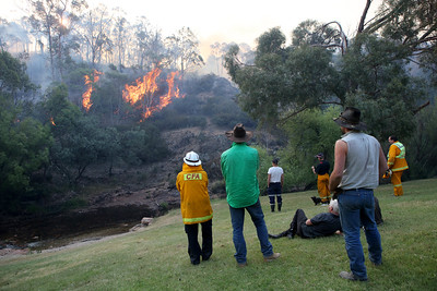 Firefighters from a joint Australian and U.S. strike team and locals watch as firefighters blackline an area on a nearby hillside in order to control a bushfire and protect nearby structures, in Alpine National Park near Omeo, Victoria, Australia, January 12, 2020. The Australian firefighters are with Country Fire Authority Australia and the U.S. team is the third rotation in for 28 days and they come from five different U.S. agencies, the U.S. Forest Service, U.S. Fish and Wildlife, Bureau of Land Management, Bureau of Indian Affairs and the National Park Services.