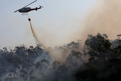 A helicopter does a water drop on a bushfire where a joint Australian and U.S. strike team blackline an area in order to control a the fire and protect nearby structures, in Alpine National Park near Omeo, Victoria, Australia, January 12, 2020. The water drop reduces the heat and slows the fire helping the team on the ground. The Australian firefighters are with Country Fire Authority Australia and the U.S. team is the third rotation in for 28 days and they come from five different U.S. agencies, the U.S. Forest Service, U.S. Fish and Wildlife, Bureau of Land Management, Bureau of Indian Affairs and the National Park Services.