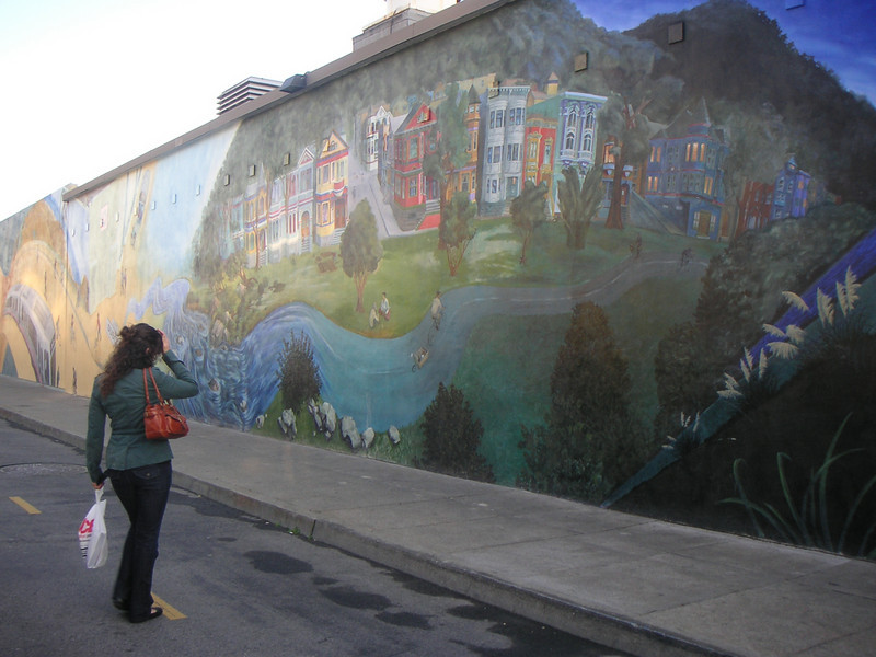 "The mural depicts destinations along the Wiggle bike route, of which the Duboce Bikeway is the beginning.  The Duboce Avenue Streetscape and Bikeway project is San Francisco's premiere car-free public space. Located in San Francisco's Castro District between Church and Market Street and adjacent to the J and N MUNI streetcar tracks, the project transformed a stark and run-down right-of-way behind a Safeway retail complex into a vibrant bikeway and pedestrian walkway. The bikeway connects cyclists traveling from downtown to what locals call, the Wiggle. As its name suggests, this bike route to Ocean Beach zigzags bicyclists around the grand hills of San Francisco allowing them to conserve energy and access the Pacific Ocean.   What makes this bikeway so unique is the 6,000 square foot mural that runs the entire length of the back wall of the Safeway. Designed by Mona Caron and commissioned by the City of San Francisco Bike Program, the <a href=""http://www.monacaron.com/mural.html""> mural</a> received the Precita Eyes Best New Mural 1999 Award.   TE funding amounting to $410,000 was used to convert this portion of Duboce Avenue from motor vehicle to bicycle use. In addition, funds paid for landscaping and interpretive signage. The project received a local match of $250,000."
