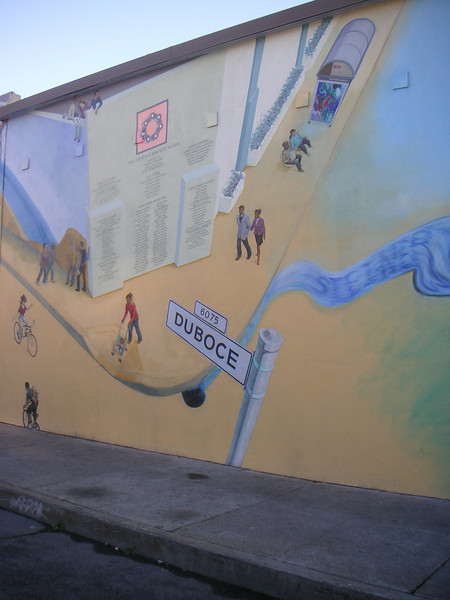 """What makes this bikeway so unique is the 6,000 square foot mural that runs the entire length of the back wall of the Safeway. Designed by Mona Caron and commissioned by the City of San Francisco Bike Program, the <a href=""""http://www.monacaron.com/mural.html""""> mural</a> received the Precita Eyes Best New Mural 1999 Award.   The Duboce Avenue Streetscape and Bikeway project is San Francisco's premiere car-free public space. Located in San Francisco's Castro District between Church and Market Street and adjacent to the J and N MUNI streetcar tracks, the project transformed a stark and run-down right-of-way behind a Safeway retail complex into a vibrant bikeway and pedestrian walkway. The bikeway connects cyclists traveling from downtown to what locals call, the Wiggle. As its name suggests, this bike route to Ocean Beach zigzags bicyclists around the grand hills of San Francisco allowing them to conserve energy and access the Pacific Ocean.   TE funding amounting to $410,000 was used to convert this portion of Duboce Avenue from motor vehicle to bicycle use. In addition, funds paid for landscaping and interpretive signage. The project received a local match of $250,000."""