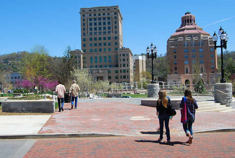 """Brick crosswalks and sidewalks provide continuity throughout Pack Square Park. This is a view of Roger McGuire Green, where events take place on the stage and amphitheater.   Pack Square Park in Asheville, North Carolina is said to be the realized dream of philanthropist George Willis Pack who donated the plot of land to the city in 1901. Nearly a century later, a water leak under Pack Square stimulated discussion to recreate and redesign Pack Square and City-County Plaza into a new public space, which has become the centerpiece of Downtown Asheville. The resulting 6.5 acre park, which sits in front of Buncombe County Courthouse and Asheville City Hall, is comprised of <a href =""""http://www.packsquarepark.org/index.php?option=com_content&task=view&id=27&Itemid=41"""""""">Pack Square</a>, <a href=""""http://www.packsquarepark.org/index.php?option=com_content&task=view&id=26&Itemid=40"""""""">Reuter Terrace</a>, and <a href= """"http://www.packsquarepark.org/index.php?option=com_content&task=view&id=25&Itemid=39"""""""">Roger McGuire Green</a>, which is the location of Bascom Lamar Lundsford Stage. The park opened on September 25, 2009.  A $140,000 Federal TE grant, procured in 2002, funded the development of the park and streetscaping around Pack Square, contiguous to three major streets: College Street, Patten Avenue, and Biltmore Avenue (US 25). In addition to the Federal funding, Pack Square Park was made possible with generous contributions by private donors."""