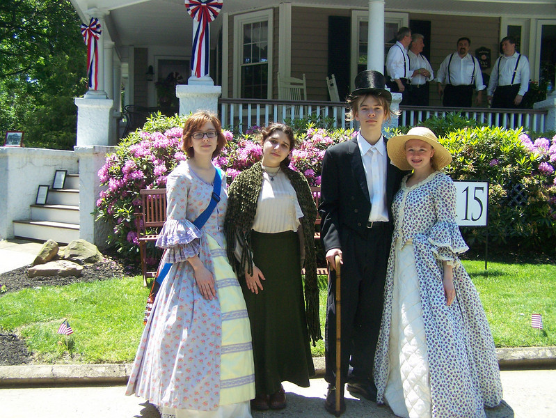 <b>Students participate in the Historic District's cultural event, greeting neighbors and visitors to Hightstown.</b>  The Stockton Street Historic District Streetscape project is the result of a community-driven and historically-focused economic stimulus plan. Even before the recession, Hightstown Borough struggled to keep its local economy afloat. Suburban development patterns made it difficult for locally-owned businesses downtown to survive. Its industry had shut its doors, and the housing crisis only added to the number of abandoned properties scarring the borough. With traditional mechanisms of economic stimulus limited, Hightstown developed a master plan that focused on re-establishing the borough as a destination town for visitors, similar to when it was a thriving railroad hub. Restoring the town's historic culture and marketing its small town pride is a central theme of the plan. The Stockton Street Historic District Streetscape project is a direct implementation strategy of this plan.   The Stockton Street Historic District is located in the Borough of Hightstown (pop. 5,216) in Mercer County, New Jersey. Seventy-six historic resources, predominantly single family dwellings, a stone church, and a historic monument contribute to this 14.35-acre district. These buildings are historically significant with varying architectural styles including early Federal, high-style Victorian, and turn-of-the-century eclectic.    The project, which is scheduled to begin construction in August 2010, seeks to restore the district's sidewalks to an eclectic mix of brick and slate. In addition, a granite curb will be constructed throughout the district to help define its boundaries by creating a consistent and distinctive look. Construction will be sensitive to unearthing carriage steps and resetting them in place along the street to convey the culture of yesteryear for visitors to the District.  The project assures handicapped accessibility throughout the public pathways, as well as street trees, gardens, and landscaping the public space consistent with plantings appropriate during the historic period of significance.  Finally, ARRA funds will support the restoration of the Civil War Monument Park, the focal point of the District. The project was awarded $1.69 million of the $19.75 million ARRA funding allocated to the State of New Jersey. This represents the third largest award in the state.