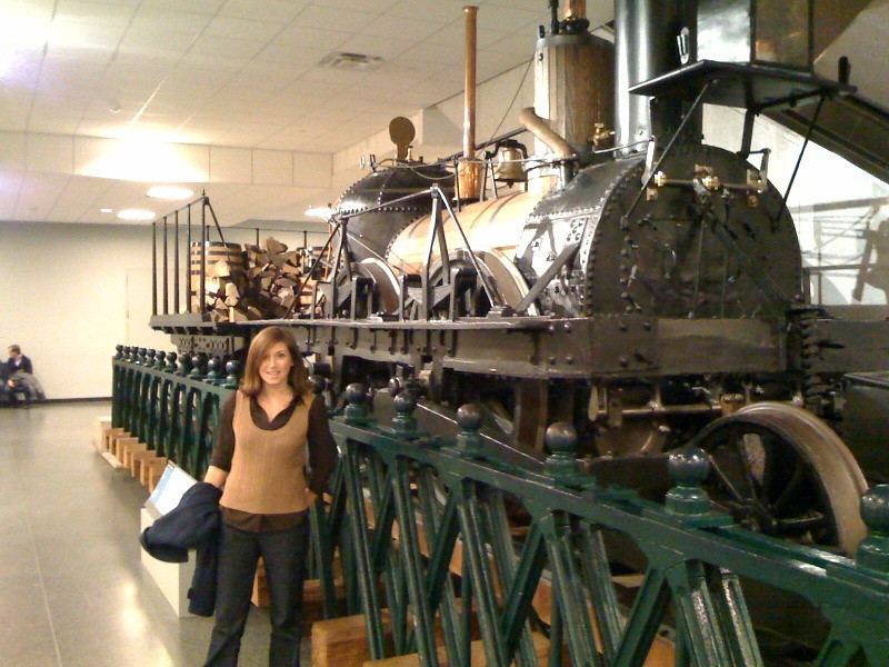 <b>A citizen of Hightstown, Amanda Rosenberg, poses in front of the John Bull steam locomotive during a visit to the Smithsonian Museum of American History. This locomotive operated along the Camden and Amboy Railroad, which ran through Hightstown. </b>  The Stockton Street Historic District Streetscape project is the result of a community-driven and historically-focused economic stimulus plan. Even before the recession, Hightstown Borough struggled to keep its local economy afloat. Suburban development patterns made it difficult for locally-owned businesses downtown to survive. Its industry had shut its doors, and the housing crisis only added to the number of abandoned properties scarring the borough. With traditional mechanisms of economic stimulus limited, Hightstown developed a master plan that focused on re-establishing the borough as a destination town for visitors, similar to when it was a thriving railroad hub. Restoring the town's historic culture and marketing its small town pride is a central theme of the plan. The Stockton Street Historic District Streetscape project is a direct implementation strategy of this plan.   The Stockton Street Historic District is located in the Borough of Hightstown (pop. 5,216) in Mercer County, New Jersey. Seventy-six historic resources, predominantly single family dwellings, a stone church, and a historic monument contribute to this 14.35-acre district. These buildings are historically significant with varying architectural styles including early Federal, high-style Victorian, and turn-of-the-century eclectic.    The project, which is scheduled to begin construction in August 2010, seeks to restore the district's sidewalks to an eclectic mix of brick and slate. In addition, a granite curb will be constructed throughout the district to help define its boundaries by creating a consistent and distinctive look. Construction will be sensitive to unearthing carriage steps and resetting them in place along the street to convey the culture of yesteryear for visitors to the District.  The project assures handicapped accessibility throughout the public pathways, as well as street trees, gardens, and landscaping the public space consistent with plantings appropriate during the historic period of significance.  Finally, ARRA funds will support the restoration of the Civil War Monument Park, the focal point of the District. The project was awarded $1.69 million of the $19.75 million ARRA funding allocated to the State of New Jersey. This represents the third largest award in the state.