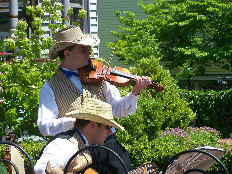 <b>Local musicians are showcased playing period music as part of cultural programming with the Historic District.</b>  The Stockton Street Historic District Streetscape project is the result of a community-driven and historically-focused economic stimulus plan. Even before the recession, Hightstown Borough struggled to keep its local economy afloat. Suburban development patterns made it difficult for locally-owned businesses downtown to survive. Its industry had shut its doors, and the housing crisis only added to the number of abandoned properties scarring the borough. With traditional mechanisms of economic stimulus limited, Hightstown developed a master plan that focused on re-establishing the borough as a destination town for visitors, similar to when it was a thriving railroad hub. Restoring the town's historic culture and marketing its small town pride is a central theme of the plan. The Stockton Street Historic District Streetscape project is a direct implementation strategy of this plan.   The Stockton Street Historic District is located in the Borough of Hightstown (pop. 5,216) in Mercer County, New Jersey. Seventy-six historic resources, predominantly single family dwellings, a stone church, and a historic monument contribute to this 14.35-acre district. These buildings are historically significant with varying architectural styles including early Federal, high-style Victorian, and turn-of-the-century eclectic.    The project, which is scheduled to begin construction in August 2010, seeks to restore the district's sidewalks to an eclectic mix of brick and slate. In addition, a granite curb will be constructed throughout the district to help define its boundaries by creating a consistent and distinctive look. Construction will be sensitive to unearthing carriage steps and resetting them in place along the street to convey the culture of yesteryear for visitors to the District.  The project assures handicapped accessibility throughout the public pathways, as well as street trees, gardens, and landscaping the public space consistent with plantings appropriate during the historic period of significance.  Finally, ARRA funds will support the restoration of the Civil War Monument Park, the focal point of the District. The project was awarded $1.69 million of the $19.75 million ARRA funding allocated to the State of New Jersey. This represents the third largest award in the state.