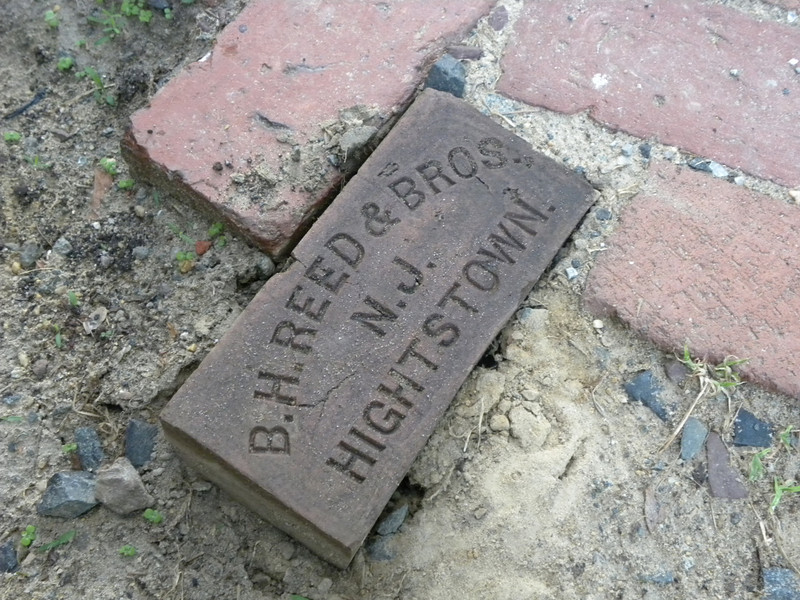 <b>While deteriorated over the last 150+ years and desperately in need of this TE project's rehabilitation, the historic brick walkways still bear the town's name.  Surviving slate walkways will also be removed and reset in place with damaged areas replaced by new slate as part of the TE historic preservation project.</b>  The Stockton Street Historic District Streetscape project is the result of a community-driven and historically-focused economic stimulus plan. Even before the recession, Hightstown Borough struggled to keep its local economy afloat. Suburban development patterns made it difficult for locally-owned businesses downtown to survive. Its industry had shut its doors, and the housing crisis only added to the number of abandoned properties scarring the borough. With traditional mechanisms of economic stimulus limited, Hightstown developed a master plan that focused on re-establishing the borough as a destination town for visitors, similar to when it was a thriving railroad hub. Restoring the town's historic culture and marketing its small town pride is a central theme of the plan. The Stockton Street Historic District Streetscape project is a direct implementation strategy of this plan.   The Stockton Street Historic District is located in the Borough of Hightstown (pop. 5,216) in Mercer County, New Jersey. Seventy-six historic resources, predominantly single family dwellings, a stone church, and a historic monument contribute to this 14.35-acre district. These buildings are historically significant with varying architectural styles including early Federal, high-style Victorian, and turn-of-the-century eclectic.    The project, which is scheduled to begin construction in August 2010, seeks to restore the district's sidewalks to an eclectic mix of brick and slate. In addition, a granite curb will be constructed throughout the district to help define its boundaries by creating a consistent and distinctive look. Construction will be sensitive to unearthing c