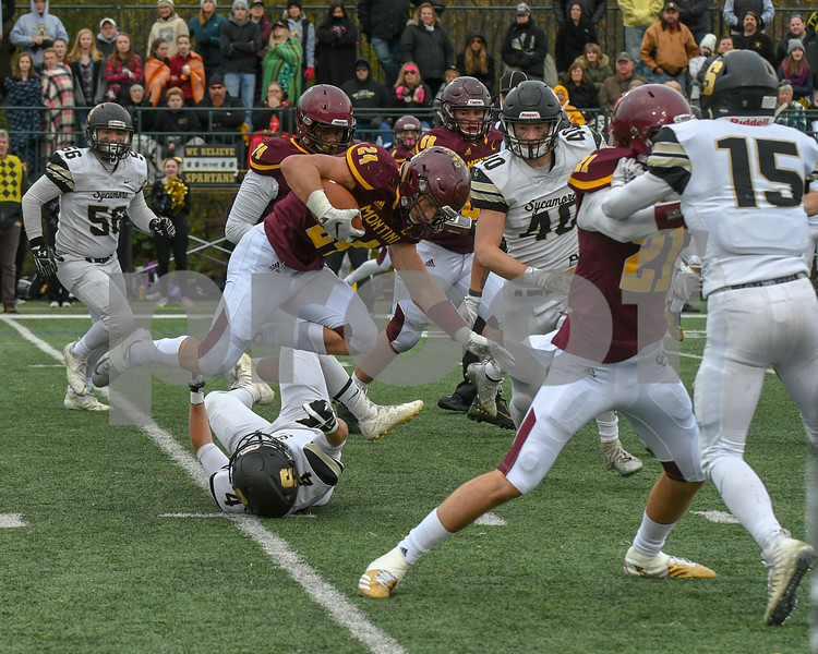 Montini Catholic Nicholas Fedanzo (24) hurdles over Sycamore Brock Alexander (4) in the fourth quarter to gain more yards.