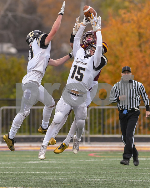 Sycamore Gavin Crofoot (15) and teammate and teammate Kyle Antos (11) help break up a pass for Montini Catholic Scott West (1) in the fourth quarter
