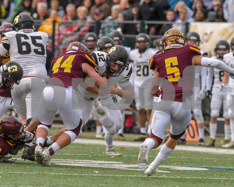 Sycamore Logan Egler (32) protects the ball in the third quarter as he was brought down agents Montini in the second week of play offs.