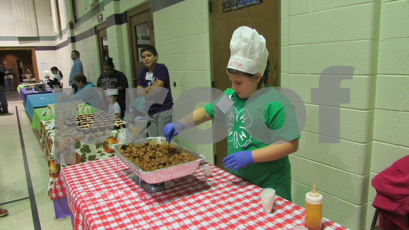 Caitlin Bennett, 9, of DeKalb serves up her award-winning meatballs Saturday night during Cooking for Kids' Sake, a fundraiser for Family Service Agency's Big Brothers Big Sisters program.