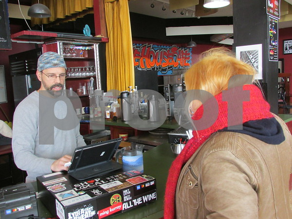 Mark Robinson (left), owner of The House Cafe in downtown DeKalb, helps a customer. Robinson has operated the cafe for a shade more than a year.
