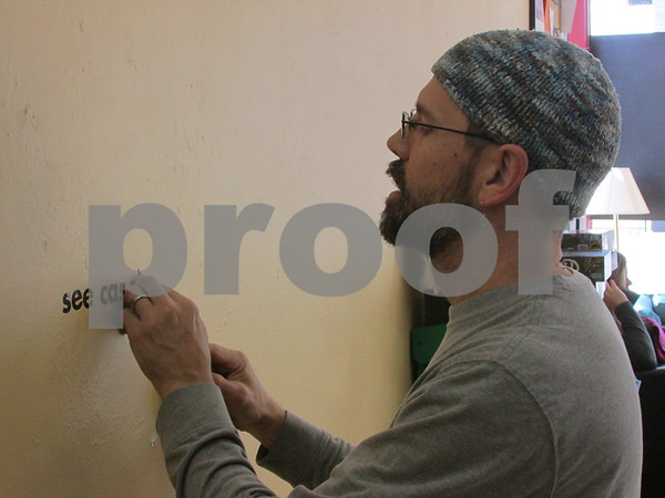 Mark Robinson, owner of The House Cafe in downtown DeKalb, removes stickers from the wall of the building. Robinson has owned the café for more than a year.