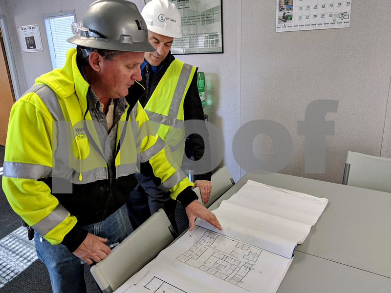 Russell Kula (left), project superintendent for the new warehouse, shows 5 Stones President Mike Pacer how the elevator will be brought into the building.