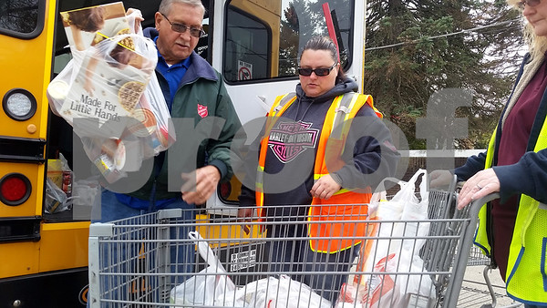 Gary Billings (from left), food pantry coordinator for The Salvation Army, 830 Grove St., DeKalb, helps First Student bus drivers Christine Urich and Denise Cagle unload nonperishable food items collected this past weekend at Hy-Vee.