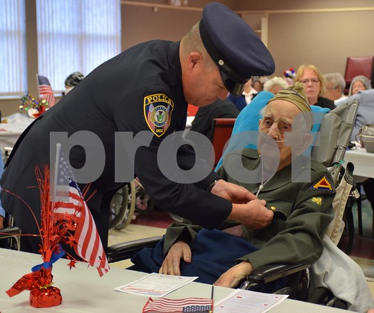 DeKalb City Police officer Jose Jaques, left, places a pin on World War II Army veteran Burton Miller's lapel Thursday, Nov. 9, during the Veterans Day Pinning Ceremony at DeKalb County Rehab and Nursing Center in DeKalb. Each of the 36 veterans in attendance received a pin and certificate to thank them for their service.
