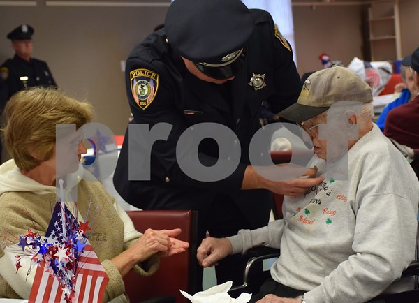 DeKalb Police Sgt. Jeff Weese, middle, places a pin on Air Force veteran Leo McDermott's lapel with the help of McDermott's daughter Pam Verbic, left, Thursday, Nov. 9, during the Veterans Day Pinning Ceremony at DeKalb County Rehab and Nursing Center in DeKalb. Each of the 36 veterans in attendance received a pin and certificate to thank them for their service.