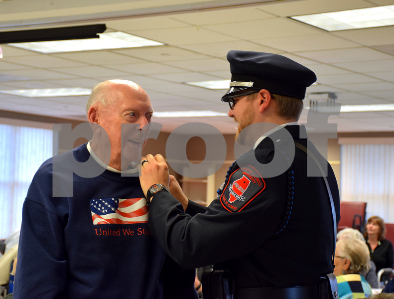Northern Illinois University police officer Matthew Lave places a pin on Korean War Air Force veteran Ken Moser's lapel Thursday during the Veterans Day Pinning Ceremony at DeKalb County Rehab and Nursing Center in DeKalb. Each of the 36 veterans in attendance received a pin and certificate to thank them for their service.