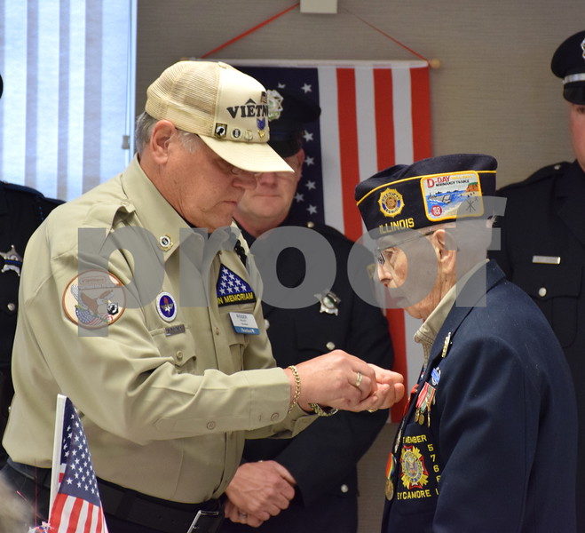 Veteran volunteer Roger Pelkey, left, places a pin on 93-year-old World War II Army veteran Donald Schoo's lapel Thursday, Nov. 9, during the Veterans Day Pinning Ceremony at DeKalb County Rehab and Nursing Center in DeKalb. Each of the 36 veterans in attendance received a pin and certificate to thank them for their service.