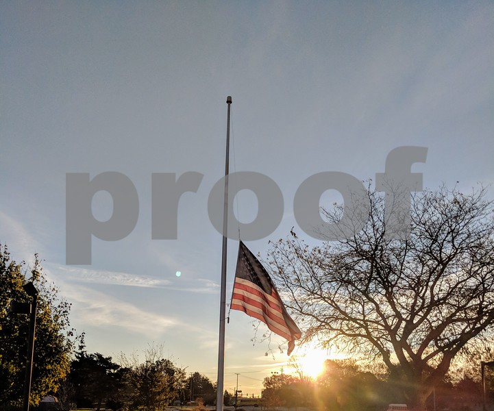 The flag is raised as the sun also rises during Friday morning's observance.