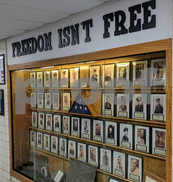 The Freedom Isn't Free display at Sycamore High School has the pictures of alumni that have died in America's wars. It also holds the plaques from previous displays the school has had. It was the end point of a flag procession through the halls of the school Friday.