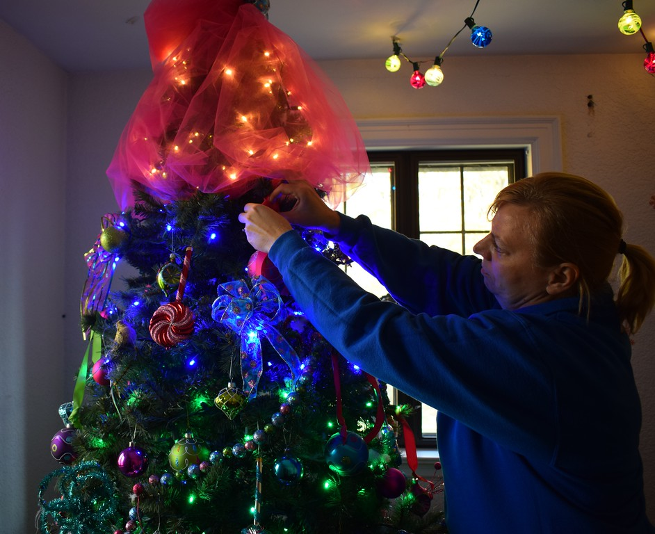. Briana Contreras � The Morning Journal <br> Annette Solet, parks and recreation supervisor decorates the Christmas tree as Trolls, in honor of the movie. This room is one of the many themed rooms in the Finwood house. The house is open from Dec. 1 until Dec. 23 from 6 p.m. to 9 p.m.