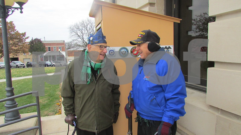 World War II veterans Ed Curzon (left) and Pete Johnson talk during their shift at the 24-hour vigil Saturday to honor veterans at the DeKalb County Courthouse.