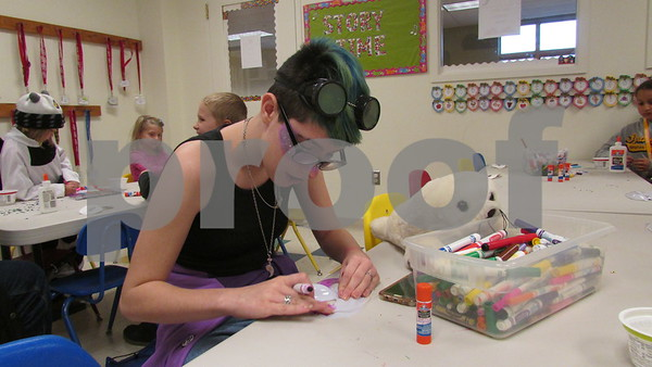 Susie Gilbert, 11, of DeKalb makes a superhero mask Saturday at the Sycamore Public Library's inaugural ComiCon event.