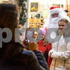 Sam Buckner for Shaw Media.<br /> Cheryl McCoy takes a picture of her granddaughters Kennedy (9) and Irish (12) with Santa in front of Sycamore Antiques on Friday November 18, 2016.