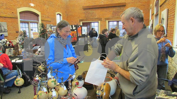 Aimee Barrows for Shaw Media<br /> Marie Stouffer of Sycamore purchases a handmade gourd ornament from artist Alec Rossiter of Sycamore.