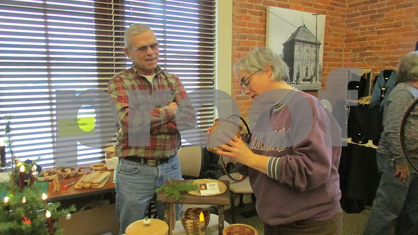 Aimee Barrows for Shaw Media<br /> Zabrina Burford of Sycamore marvels at a wood segmented bowl made by artist Jack Kuhn of Clare on Saturday at the Kish Valley Art League Holiday Arts and Crafts Market.
