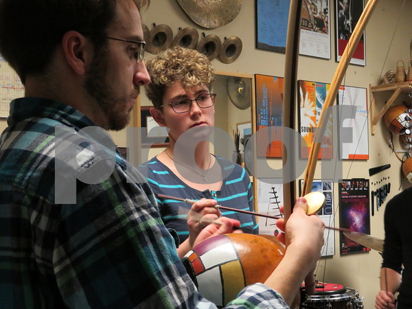 Arcomusical ensemble members Kyle Flens (left) and Alexis Lamb play a piece during a rehearsal Sunday for the berimbau musical group Arcomusical. The ensemble is preparing for Christmas concerts this week at the DeKalb Public Library.
