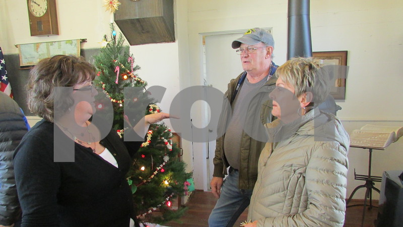 Jennifer Parsons (left) chats with visitors Jim and Gloria Ryan of Sycamore during the Holiday Open House on Saturday at North Grove School in Sycamore.