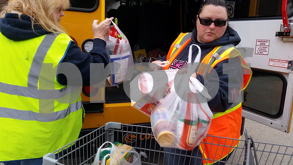 Christine Urich (right) and Denise Cagle, bus drivers for First Student, unload nonperishable food items Nov. 7 in The Salvation Army parking lot.