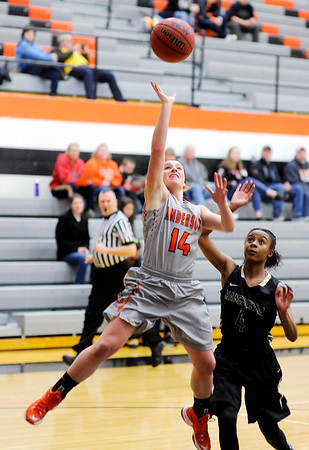 Don Knight | The Herald Bulletin<br /> Anderson University's Kaycee Strunk drives past Manchester's Faith Alexis-Graham for a layup on Wednesday.