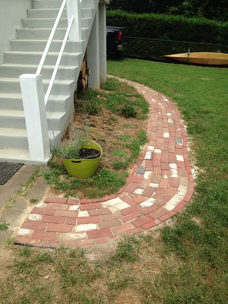 We also built this little path from the driveway to the patio/deck steps. 50% of the bricks, we found on the property. 25% we bought at the home salvage place for very cheap. The rest we got at Home Depot.<br /> <br /> In a few years, the grass and strawberries will have grown nicely over the edges. We have plans for the dirt area behind it. That green bucket has Russian sage, which has pretty purple flowers and is deer-resistant. Maybe more of that and some bushy red flowers called Bee balm. It will not stay bare dirt next year.