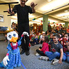 John McDonough of Pumpernickle Puppets walks through a crowd of children with one of his characters during the 11th annual celebration of the Martin T. Feldman Children's Room inside the Leominster Public Library on Sunday.  SENTINEL & ENTERPRISE JEFF PORTER