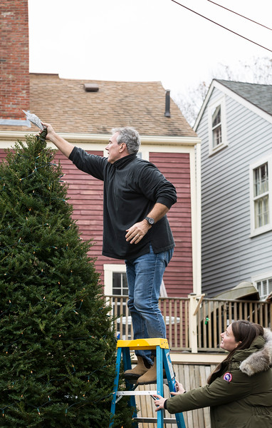 Luke, left, and Kyle Gaffney of Marblehead put the star on top of their Christmas tree outside of their home on Saturday.