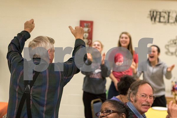 Sam Buckner for Shaw Media.<br /> Carl Ryan raises his hands in the air while getting an applause NIU softball players after getting the award for best use of color on his cookies at Club 55 on Friday December 1, 2017.