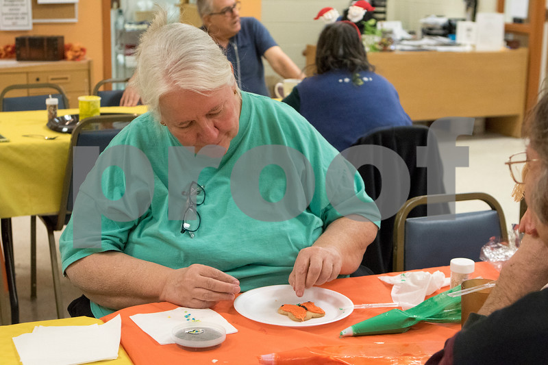 Sam Buckner for Shaw Media.<br /> Susan Woodyard adds sprinkles to her butterfly cookie design at Club 55 on Friday December 1, 2017.