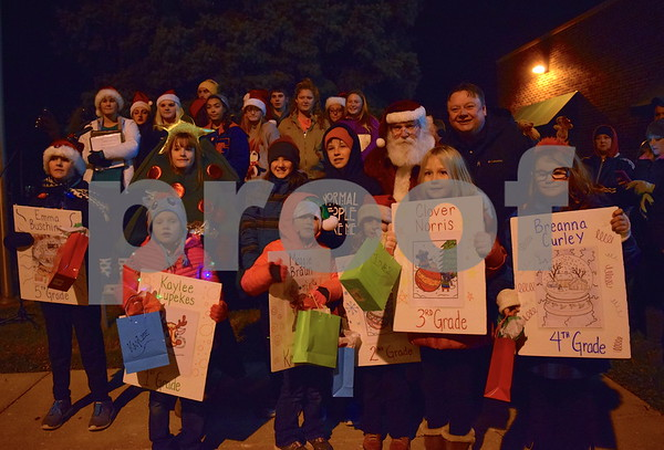 Santa Claus awarded the winners of the grade school coloring contest and led the countdown for the tree-lighting ceremony in front of Heartland Bank during Celebrate the Season, held in downtown Genoa on Friday.
