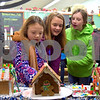 Best friends Ruby Mulvaney (center) and Rylie Stoffregen (right), both 11 and from Genoa, and Ruby's 7-year-old sister Lily (left) look at the winners of the gingerbread house decorating contest at Latsis Bakery during Celebrate the Season, held Friday, Dec. 2.