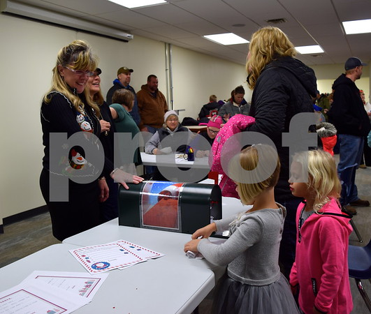 Four-year-old Samanta Mueller of Poplar Grove (left) and her 5-year-old cousin Paysen Mueller send their letters to Santa Claus at Genoa Public Library during Celebrate the Season on Friday. Both cousins asked Santa for a horse.