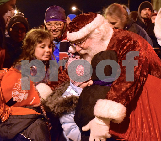 Children rush to gather around and hug Santa Claus as he arrived during the end of Celebrate the Season's Jingle Bell Parade. The event sponsored by the Genoa Area Chamber of Commerce was held in downtown Genoa from 6 to 8 p.m. Friday.