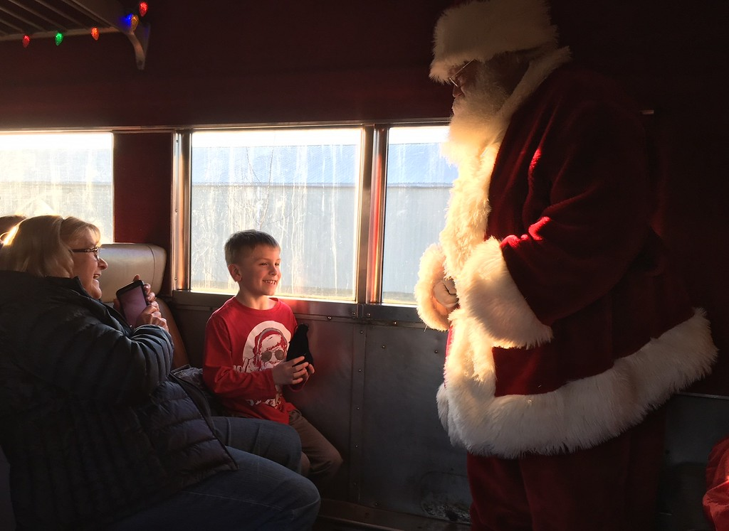 . Richard Payerchin - The Morning Journal <br> Casey Johnson, 7, of North Olmsted, receives his jingle bell from Santa Claus as his grandmother, Debbie Stec of Columbia Station, looks on during the Santa Train ride Dec. 2, 2017. The Santa Train is in its second year on the Lorain & West Virginia Railway of the Lake Shore Railway Association in Wellington.