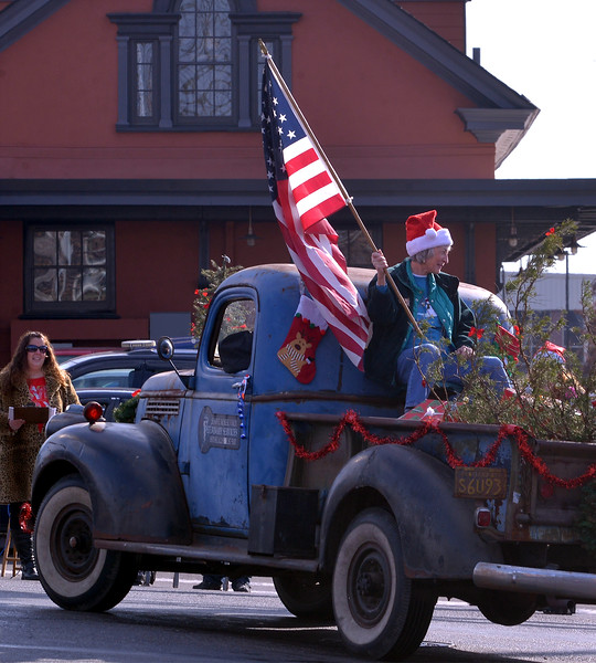 A woman waves an American flag in the bed of an antique pickup truck during the Souderton Holiday Parade Dec. 2, 2017. (Bob Raines--Digital First Media)