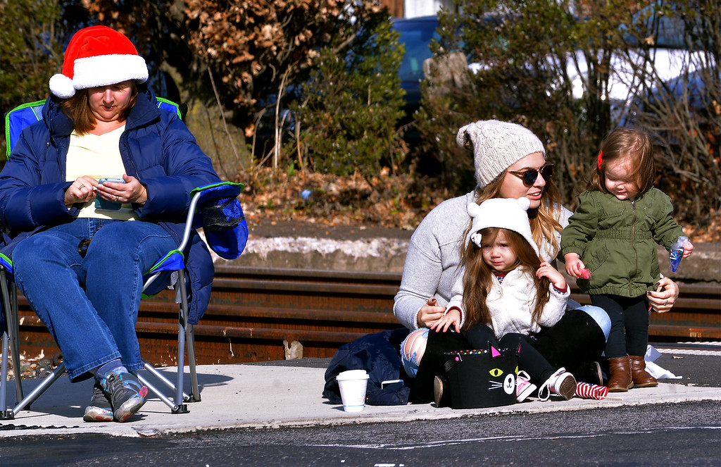 . A woman and her two daughters wait for the parade as another woman sends a text at the Souderton Holiday Parade Dec. 2, 2017. (Bob Raines--Digital First Media)