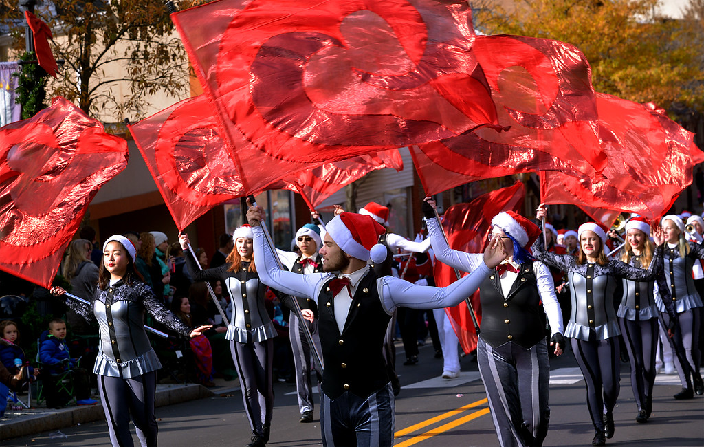 . The Souderton Marching Band Color Guard precede the musicians in a swirl  of red at the Souderton Holiday Parade Dec. 2, 2017. (Bob Raines--Digital First Media)