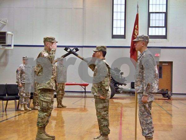 Capt. Robert Lemmon (left) assumes command and instructs 1st Sgt. Jason Kwak to secure the troops as Spc. Dominic Lopez bears the guidon.