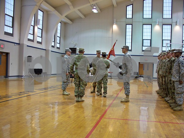 Capt. Robert Lemmon (center) passes the guidon to 1st Sgt. Jason Kwak as Lt. Col. Daniel Williams (left), departing Capt. Ryan Colmone and members of the Alpha Battery 2nd Battalion, 122nd Field Artillery Regiment look on. Lemmon assumed command of the battery Saturday morning.